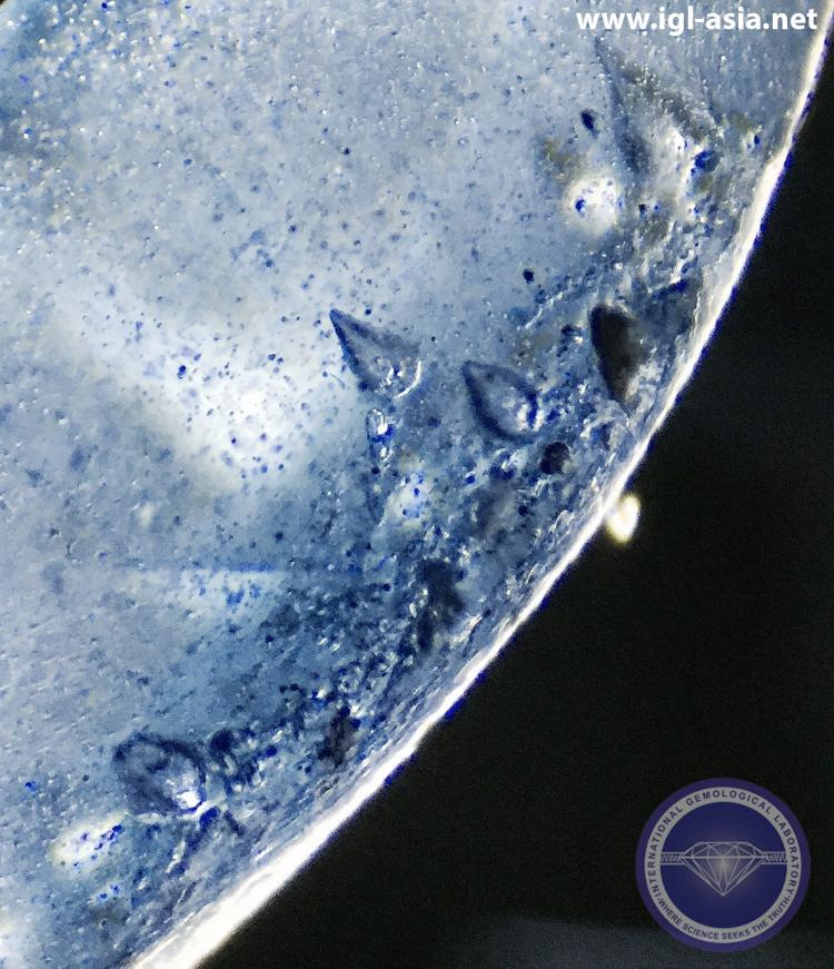 """Rain Drop"" bubbles and numerous tiny Gas Bubbles with streaks of blue color in a flame-fusion Synthetic Sapphire - Photo by: Naveed Zafar G.G., AJP ("